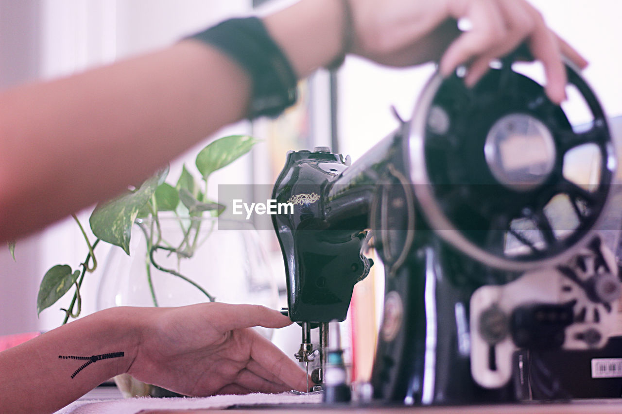 Cropped image of hands sewing on machine