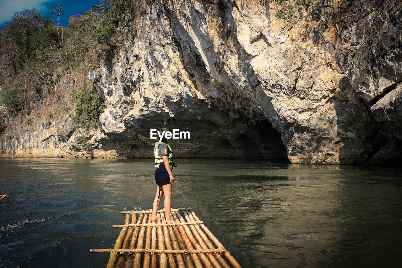 Side view of woman standing on wooden raft in sea against rock formation