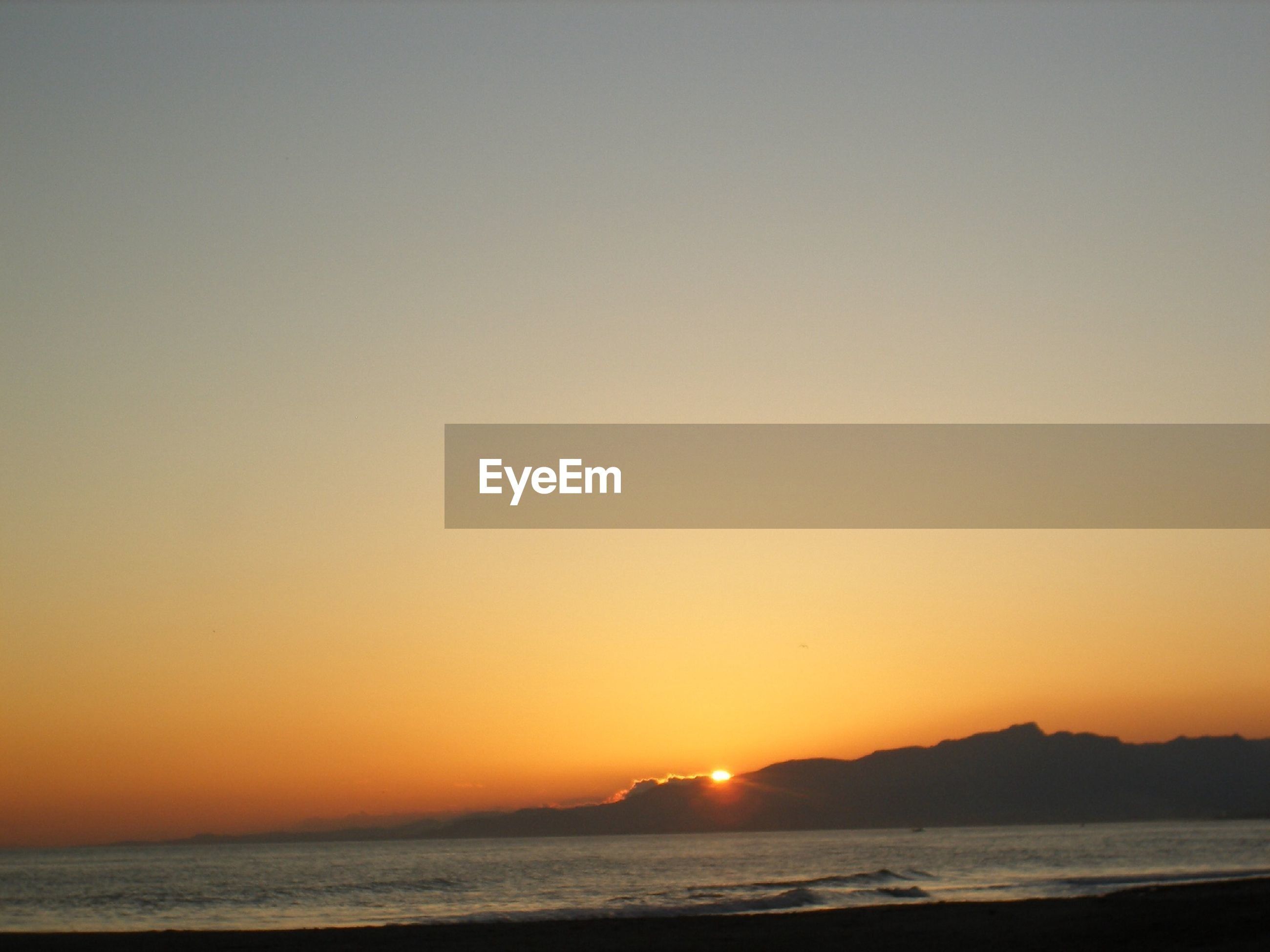 Scenic view of beach during sunset against clear sky