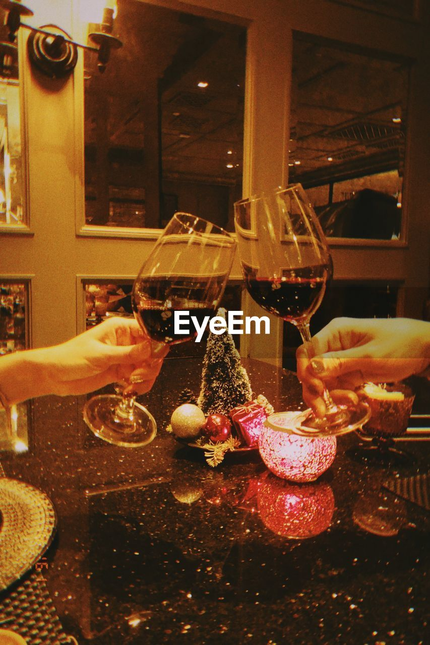 food and drink, human hand, hand, alcohol, refreshment, drink, glass, human body part, food, wine, real people, indoors, wineglass, table, freshness, people, celebration, holding, lifestyles, celebratory toast, red wine, finger
