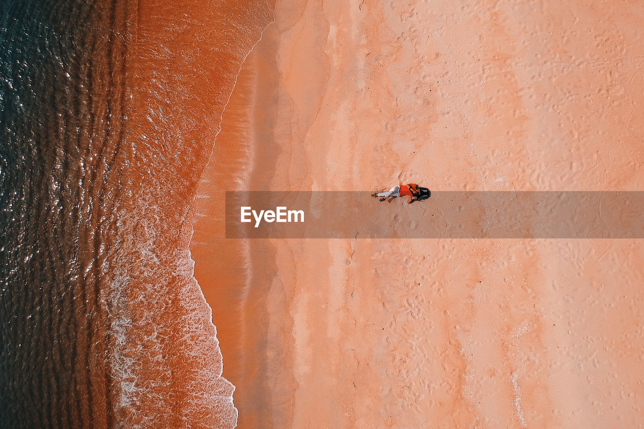 Aerial View Of Woman Lying On Beach