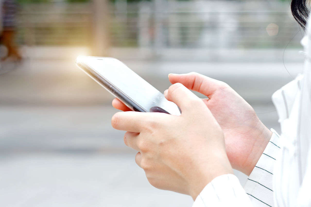Cropped hands of businesswoman using smart phone