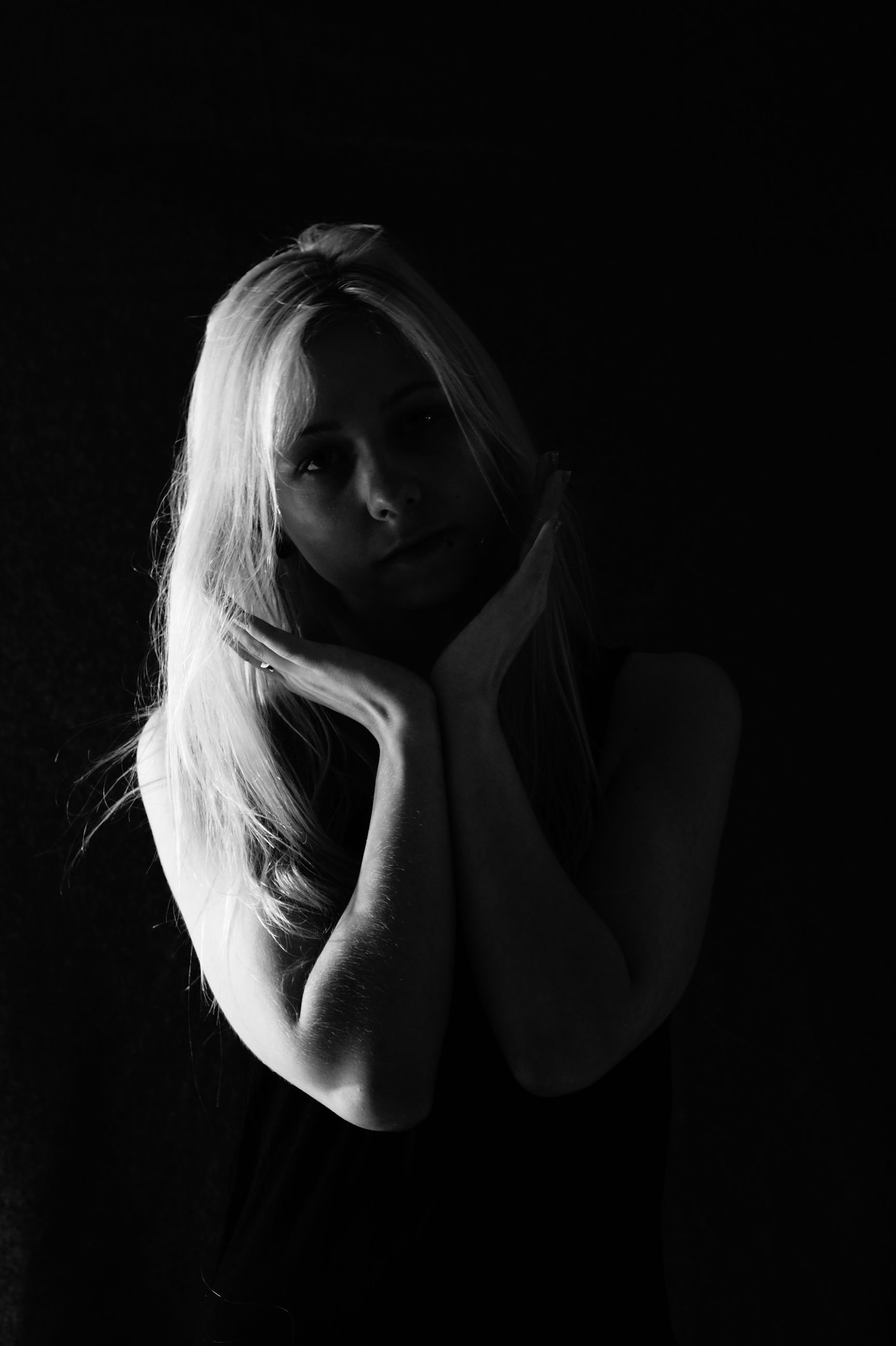 Portrait of a beautiful young woman gesturing against black background