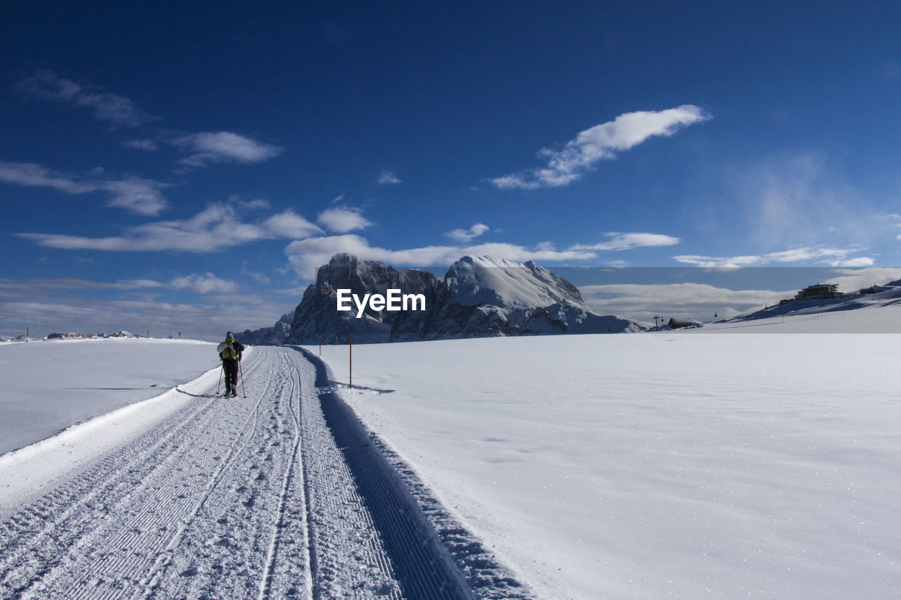 Woman walking on snowy land against snowcapped mountains