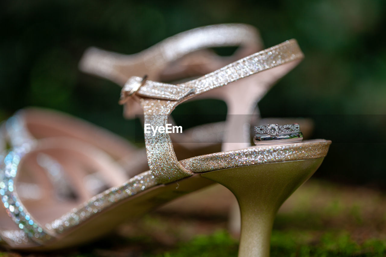 Close-Up Of Wedding Ring With Sandal On Field