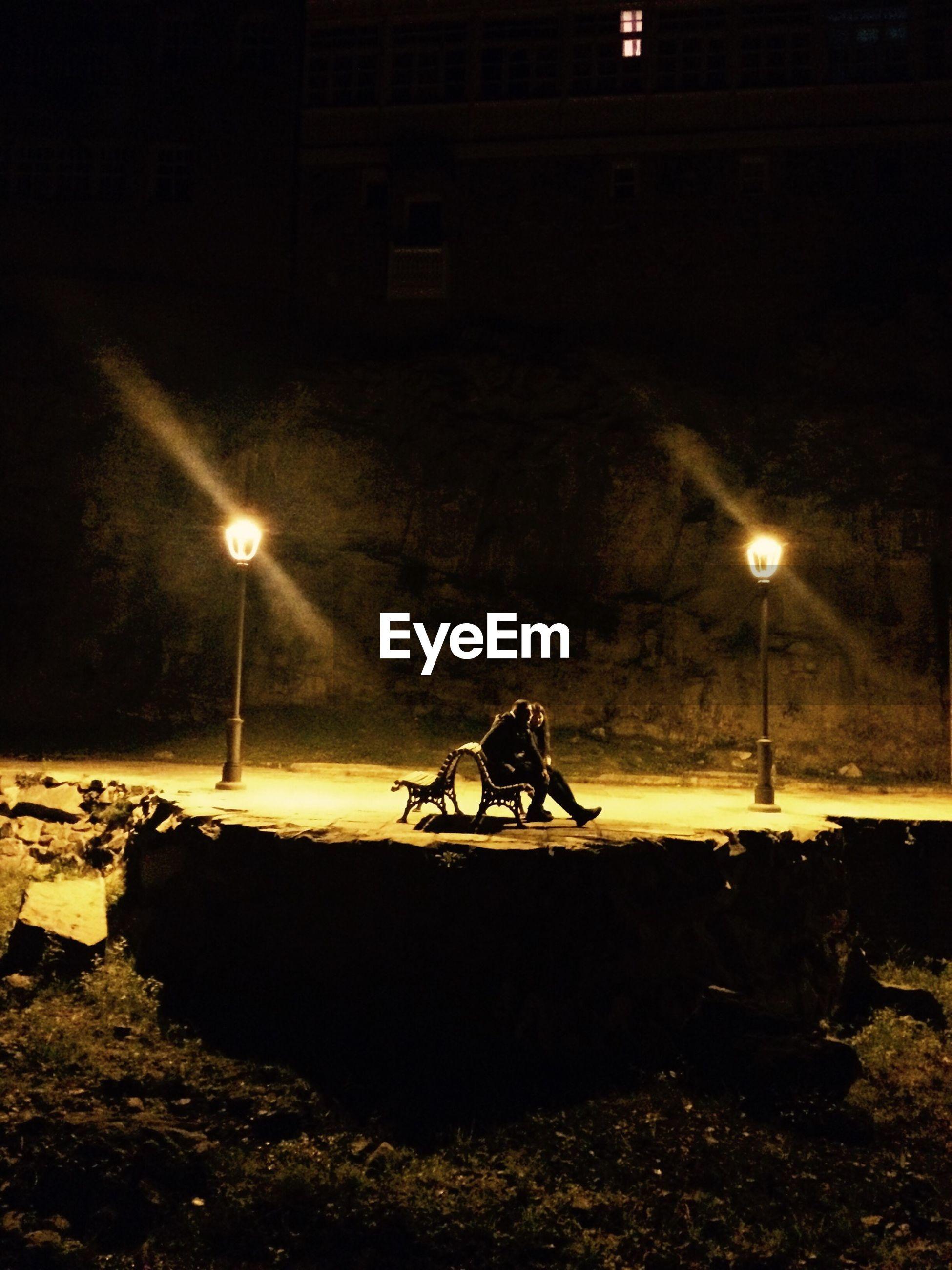 Couple sitting on bench amidst illuminated street lights at night