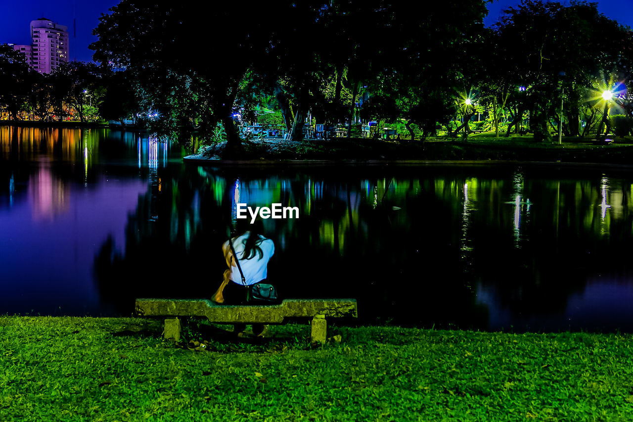 sitting, one person, plant, real people, tree, illuminated, lake, full length, reflection, nature, water, lifestyles, night, leisure activity, seat, women, young adult, green color, outdoors, contemplation