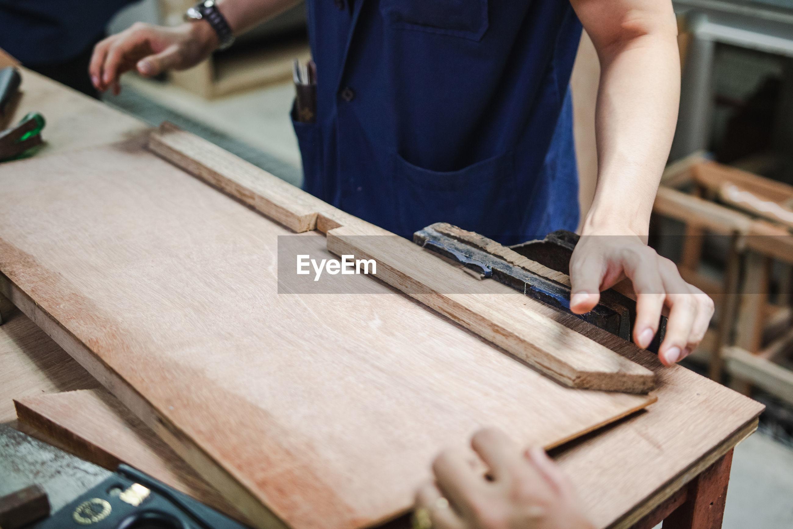 Midsection of carpenter making furniture in carpentry workshop