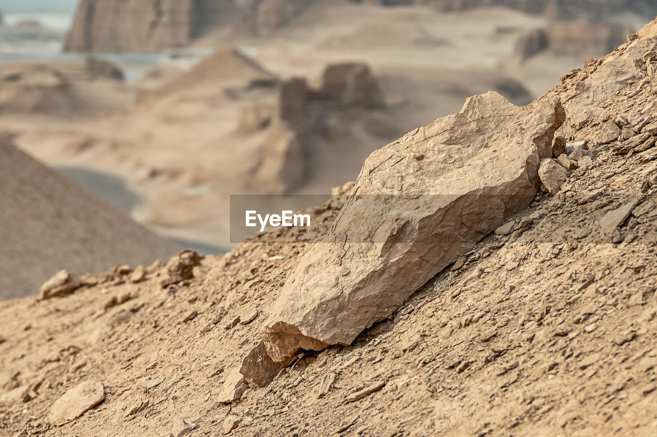 CLOSE-UP OF ROCK FORMATION ON SAND LAND