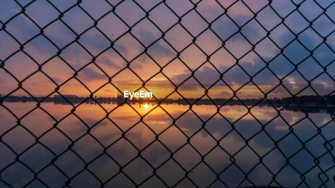 sky, sunset, fence, chainlink fence, protection, security, barrier, boundary, metal, safety, nature, scenics - nature, no people, orange color, beauty in nature, outdoors, water, cloud - sky, pattern, backgrounds, crisscross