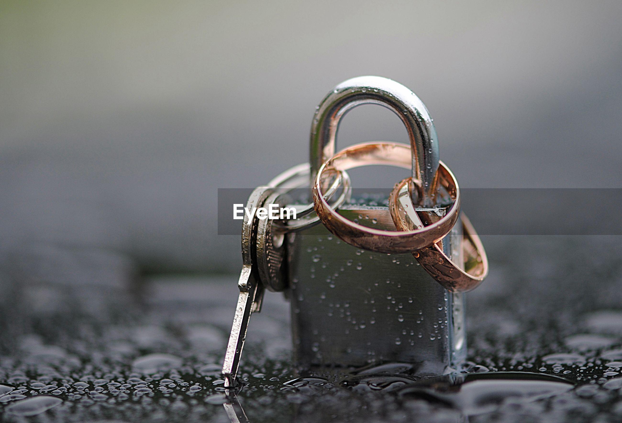 Close-up of wedding rings locked in padlock