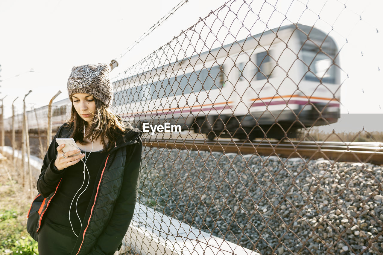 Woman Using Phone While Standing By Chainlink Fence Against Train