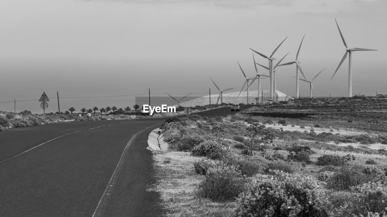 renewable energy, alternative energy, road, sky, fuel and power generation, environmental conservation, transportation, wind turbine, environment, turbine, wind power, nature, day, landscape, no people, land, the way forward, sign, outdoors, field