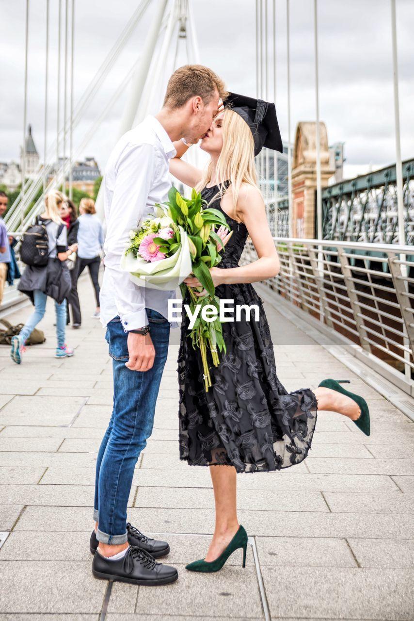 Woman Wearing Mortarboard And Holding Bouquet Kissing Boyfriend On Bridge
