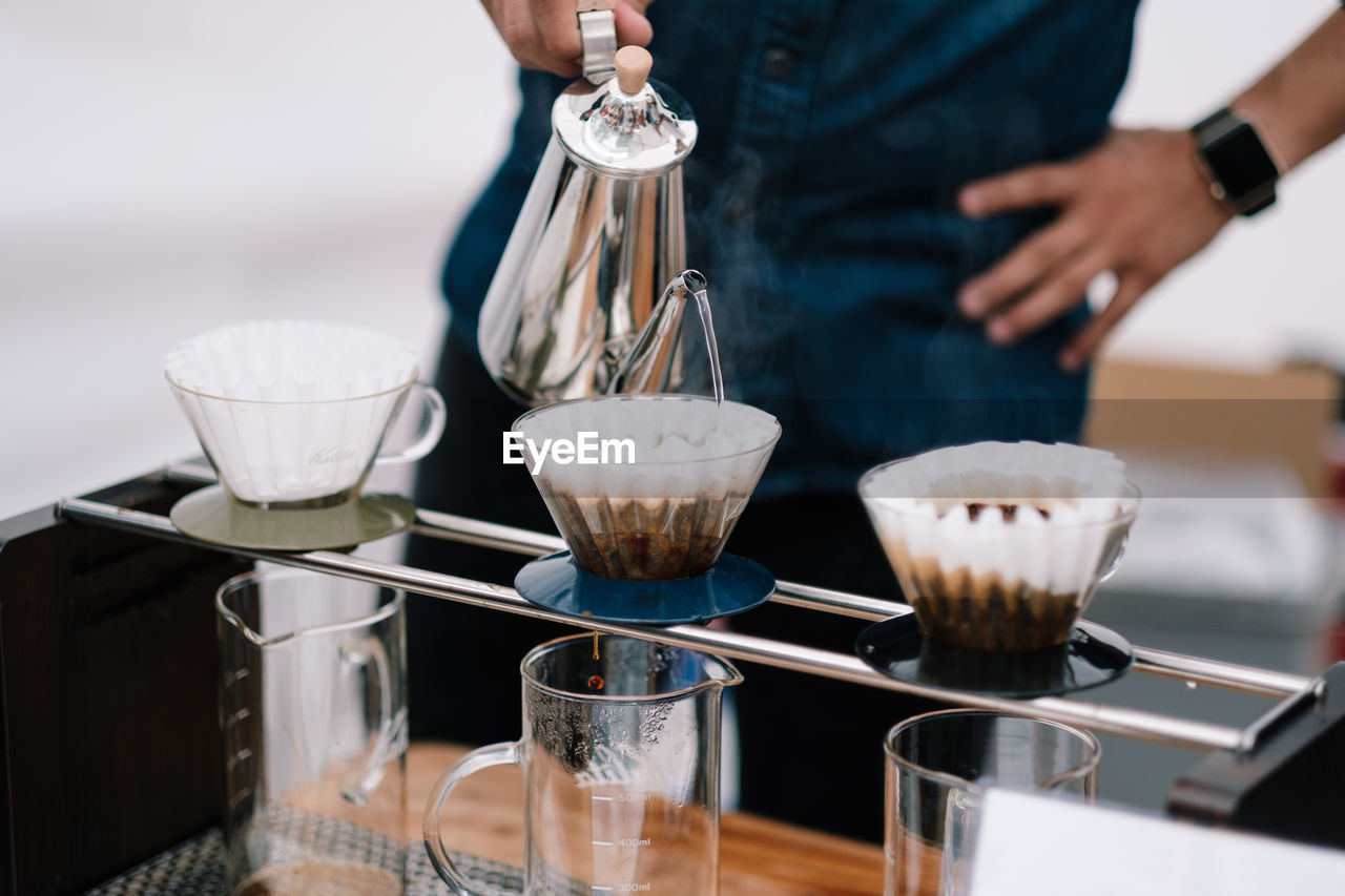 Midsection of barista pouring water in coffee cup