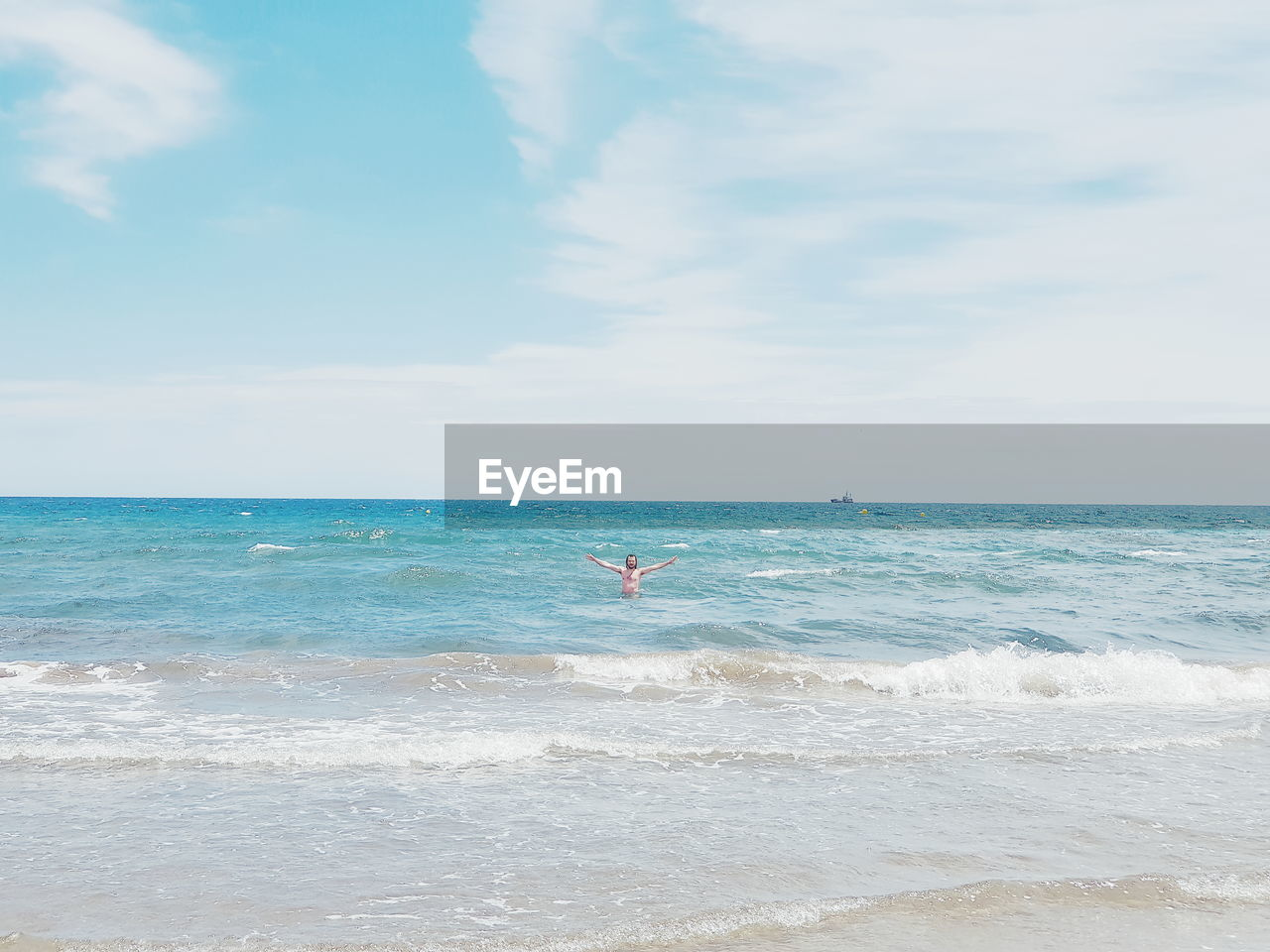 Mid distance of man swimming in sea against sky