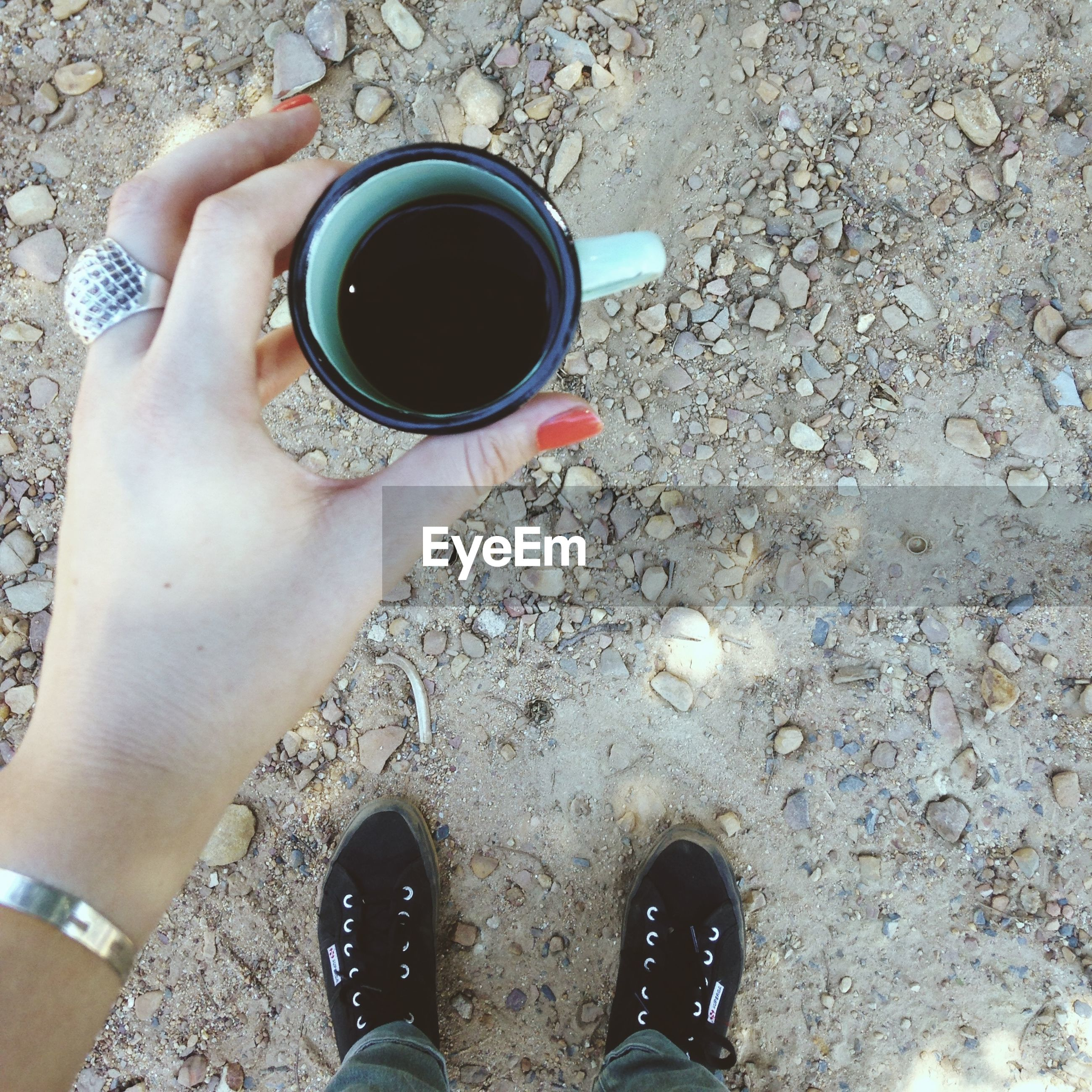 Low section of woman holding black coffee on field
