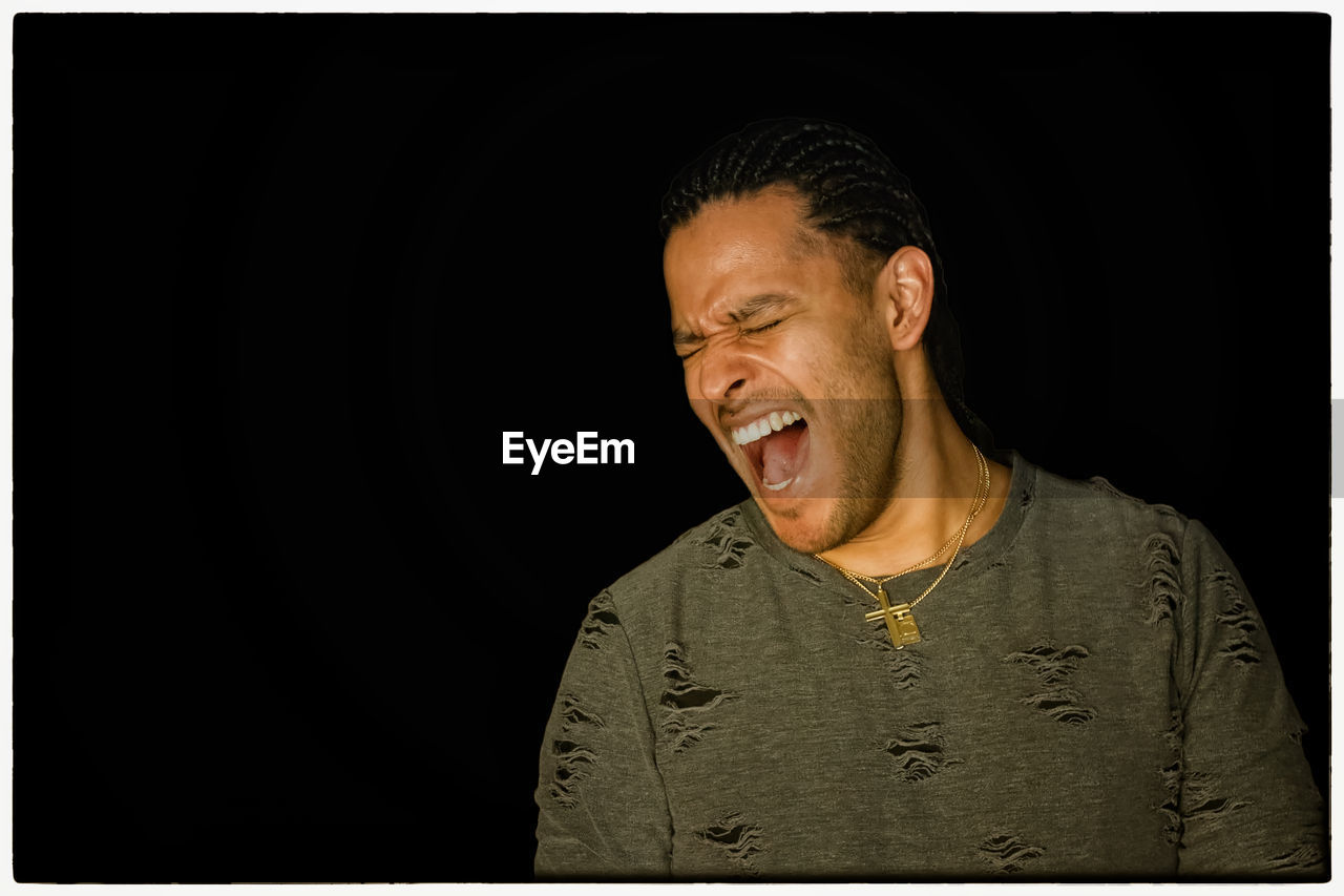 studio shot, mouth open, black background, one person, real people, men, young adult, close-up, day, people