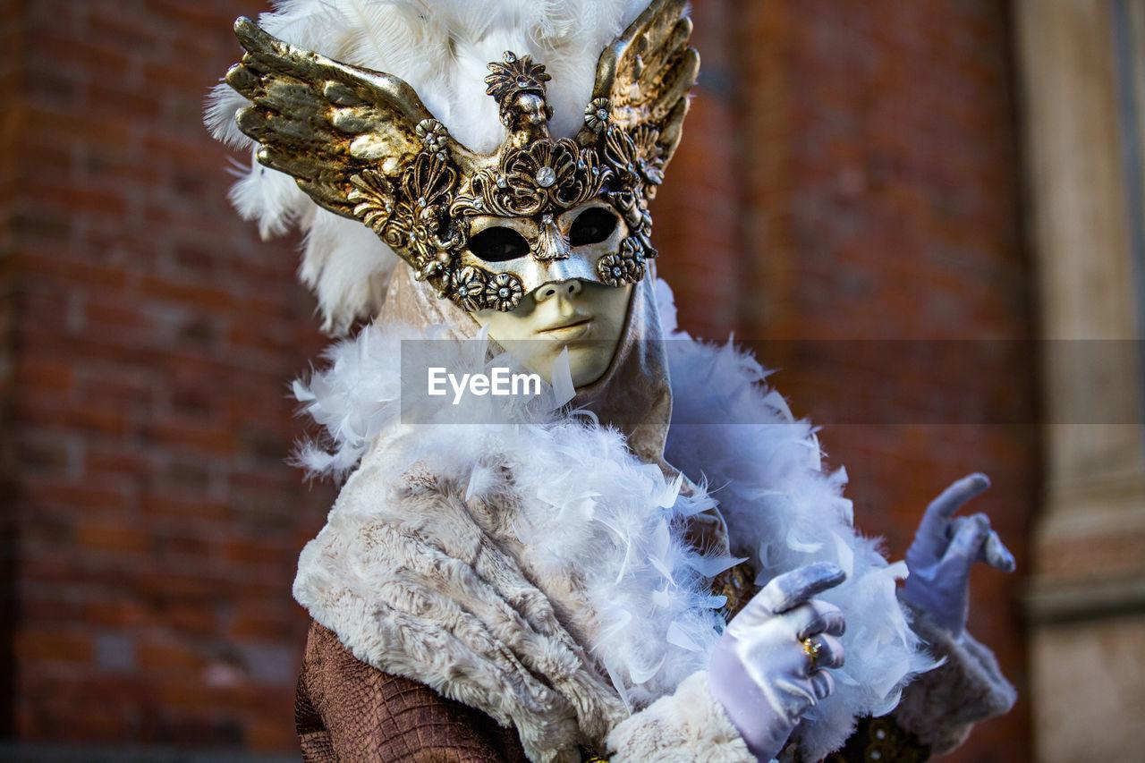 Portrait Of Man Wearing Venetian Mask Against Brick Wall