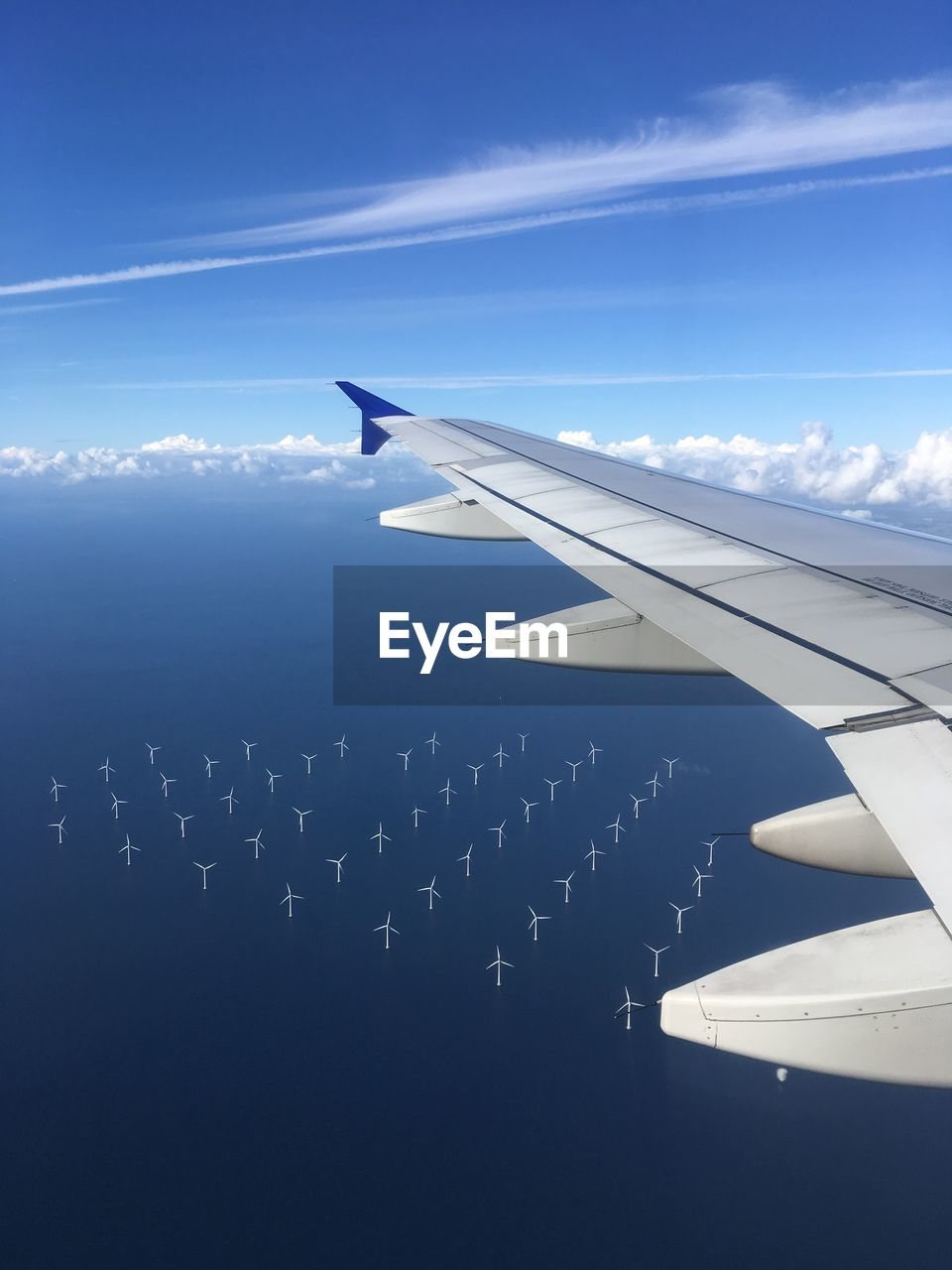 Airplane Flying In Sky Above Sea With Wind Turbines