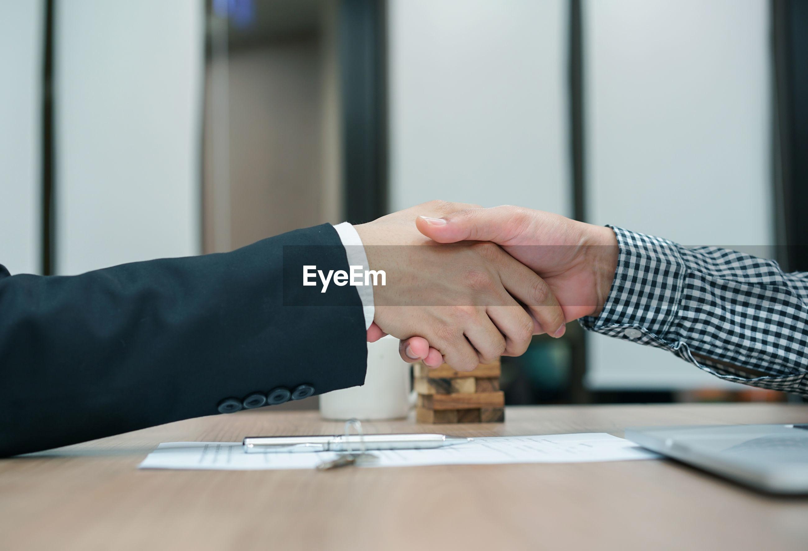 Cropped image of businessmen shaking hands at desk in office
