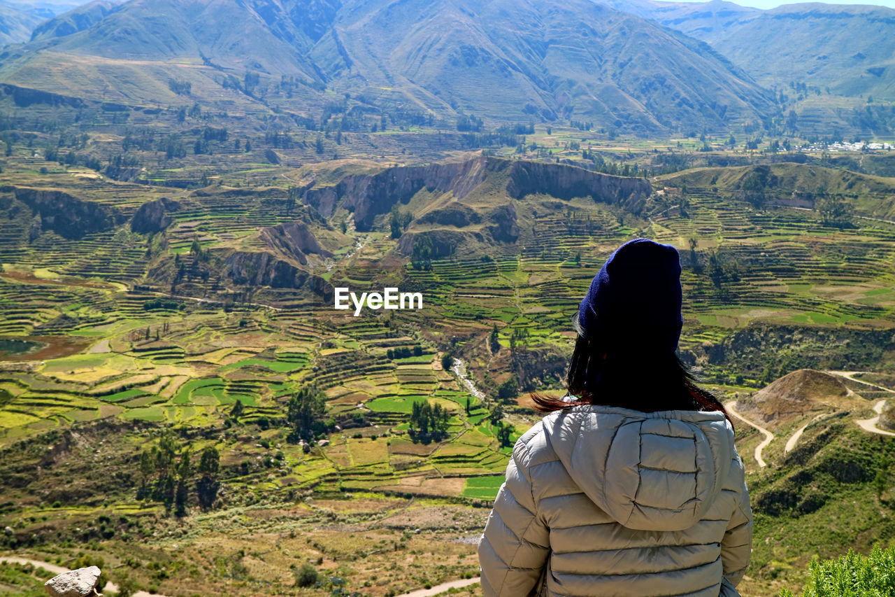 Rear view of woman wearing warm clothing while looking at landscape