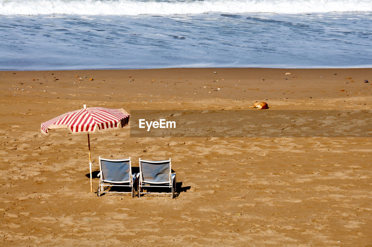 Deck Chairs And Parasol On Sea Shore At Beach