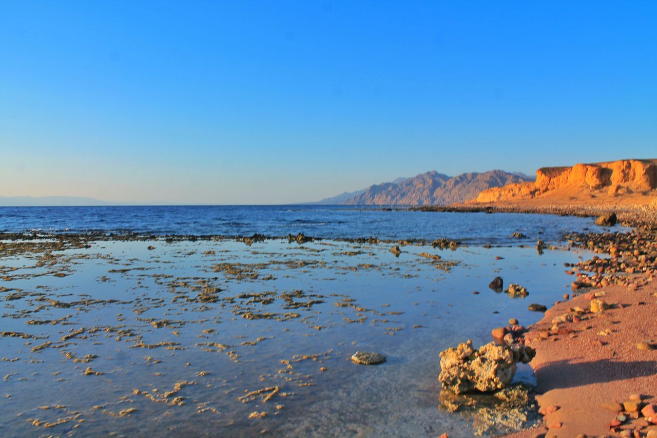water, sky, sea, clear sky, scenics - nature, beauty in nature, land, copy space, beach, tranquility, tranquil scene, blue, nature, horizon over water, horizon, no people, non-urban scene, idyllic, rock, outdoors