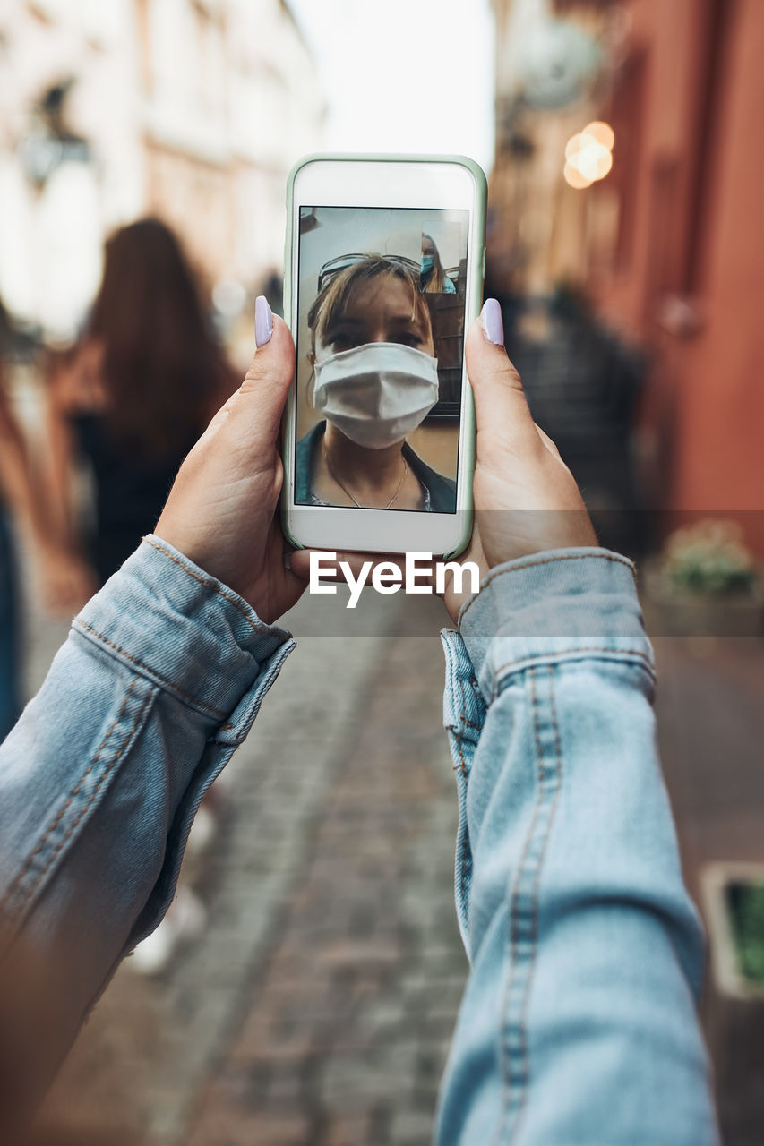 Young woman having video call talking while walking downtown chatting with friend wearing a mask