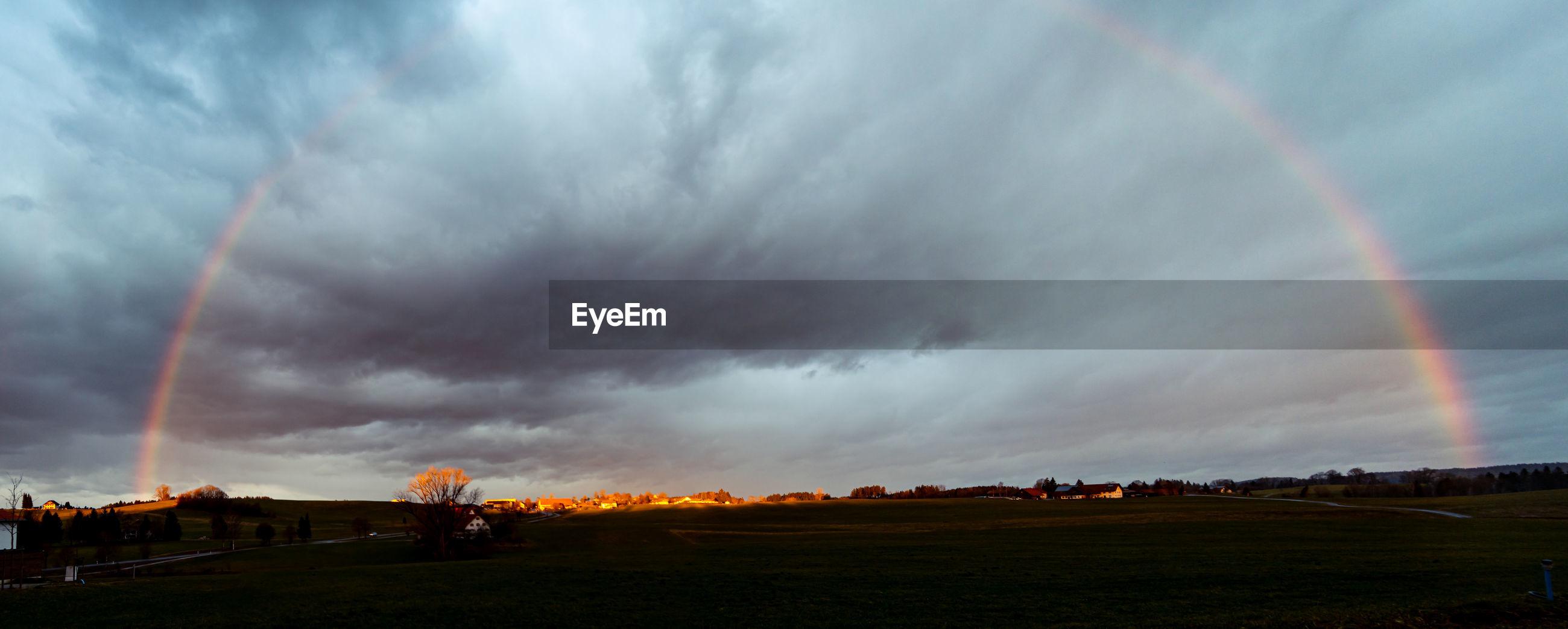 PANORAMIC VIEW OF RAINBOW OVER FIELD