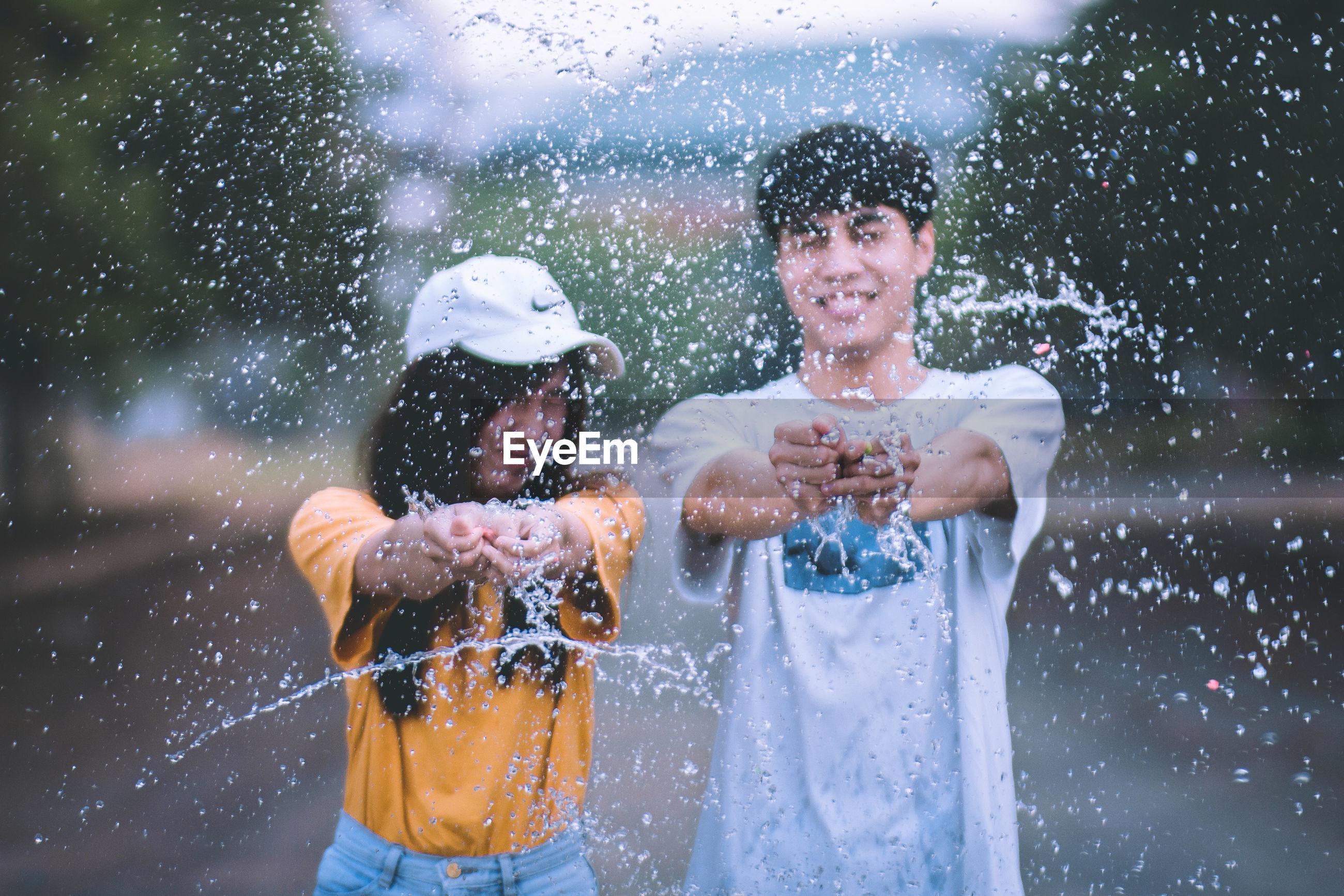Portrait of smiling couple splashing water on road
