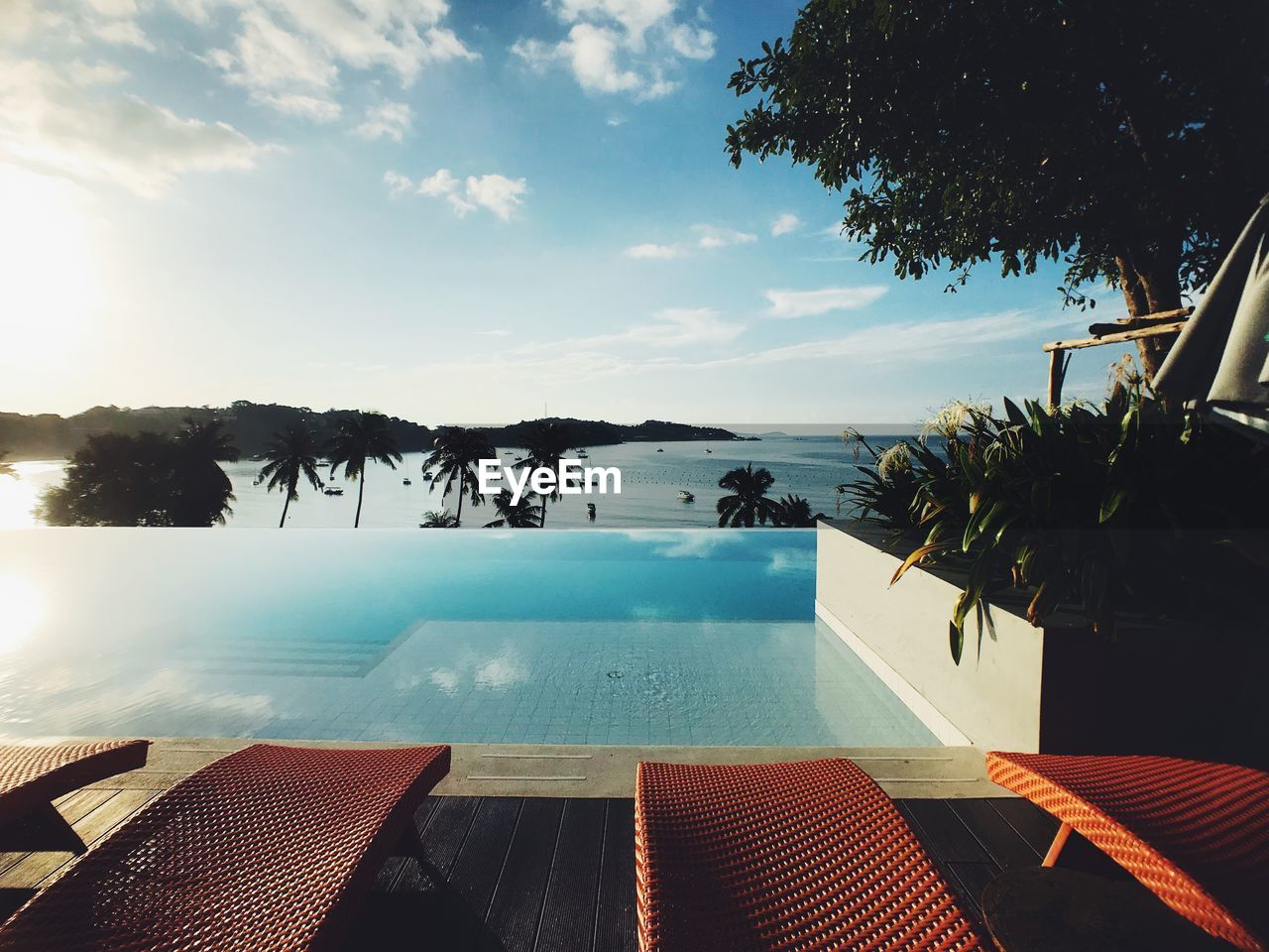 swimming pool, water, sky, plant, pool, nature, chair, tree, cloud - sky, no people, absence, tourist resort, seat, day, beauty in nature, sea, tranquil scene, table, tranquility, outdoors, luxury