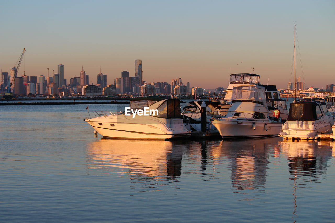 nautical vessel, transportation, reflection, mode of transport, waterfront, water, sunset, moored, no people, building exterior, architecture, built structure, sky, skyscraper, outdoors, city, sea, nature, yacht, urban skyline, day