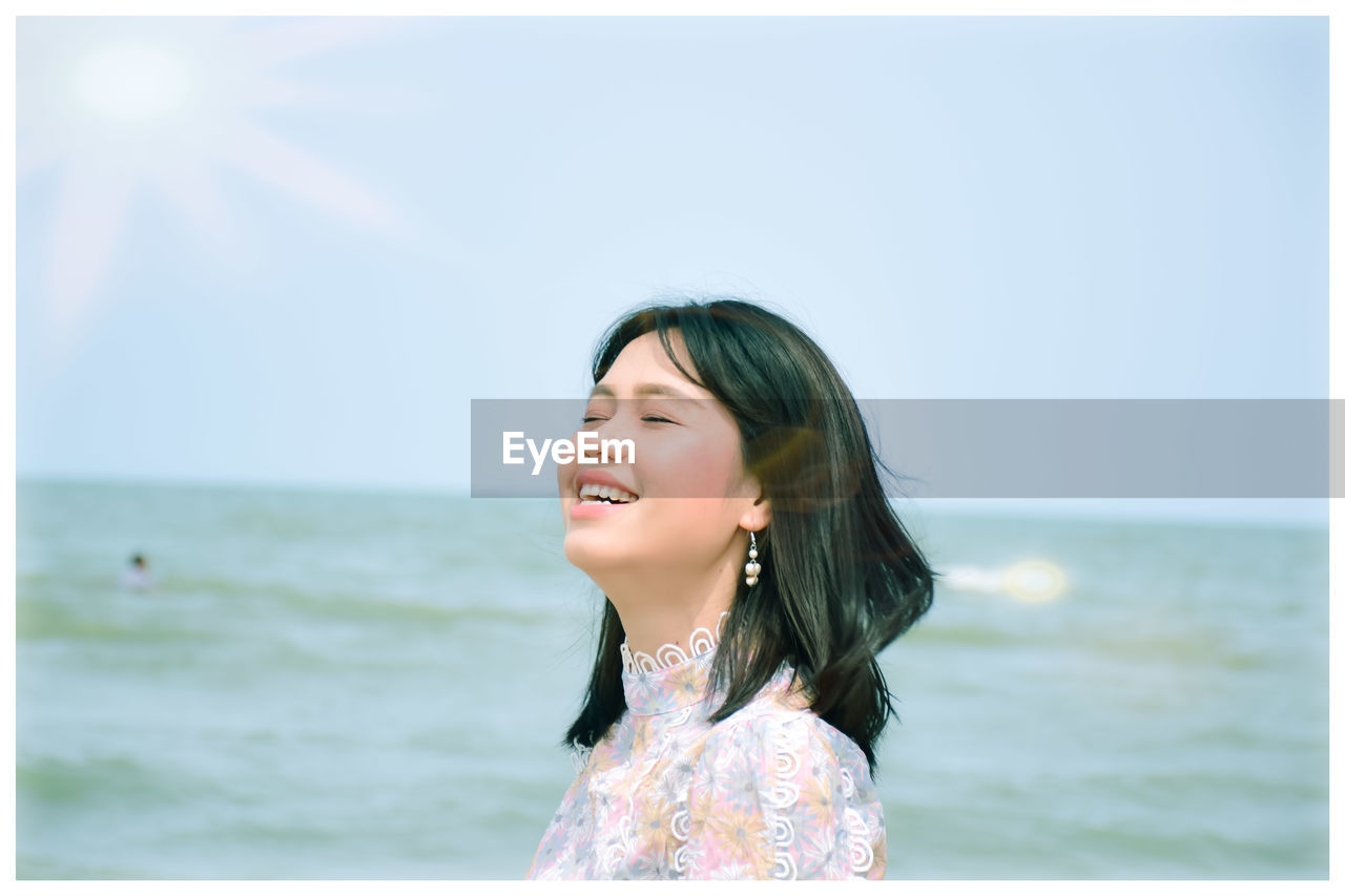 Smiling woman with eyes closed against seascape and sky