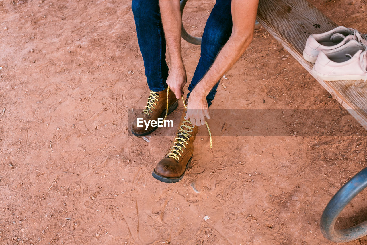Low section of person tying shoelace on mud