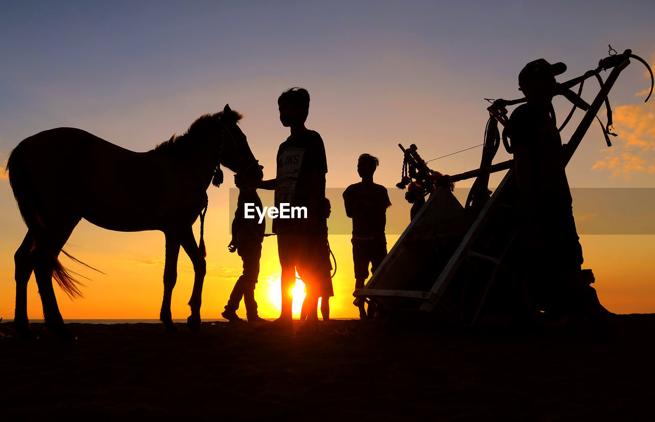 Silhouette Boys With Horse At Cart At Beach Against Sky During Sunset