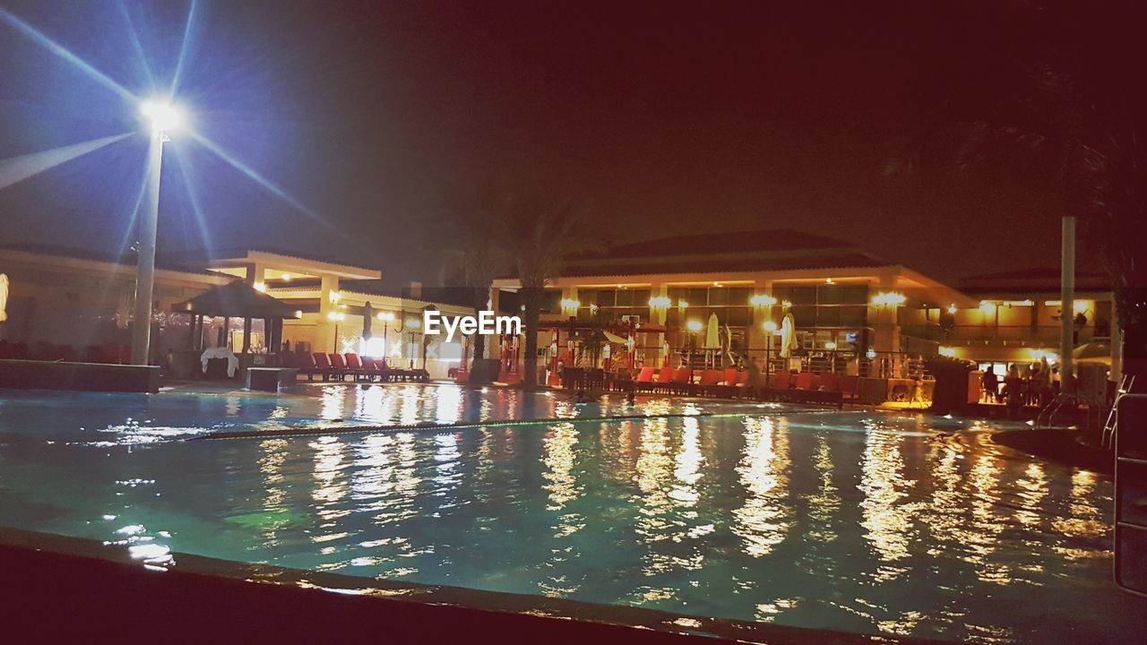 water, night, illuminated, swimming pool, built structure, architecture, building exterior, outdoors, vacations, real people, sky, nature