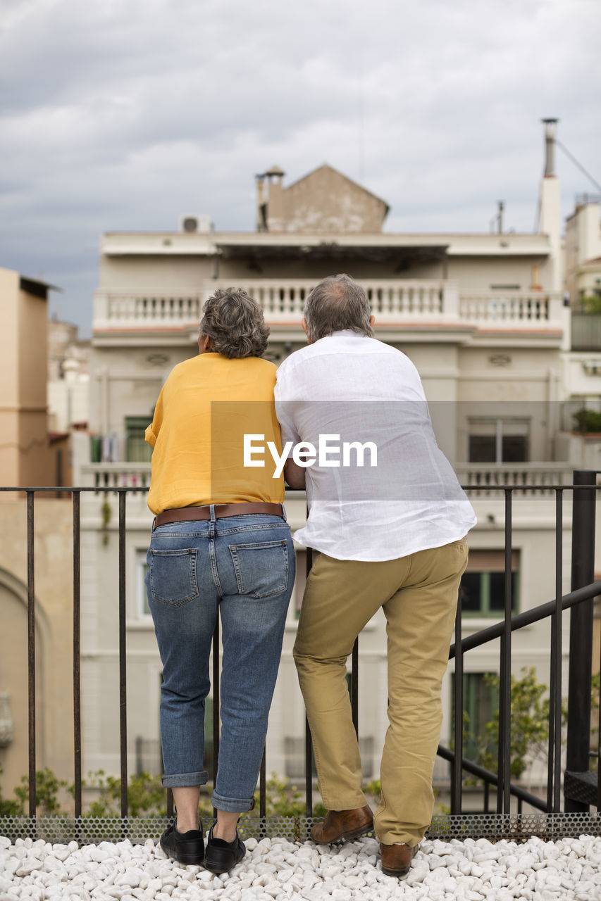 rear view, architecture, built structure, building exterior, two people, real people, men, togetherness, full length, adult, lifestyles, casual clothing, couple - relationship, people, bonding, women, day, leisure activity, sky, love, outdoors, positive emotion, arm around
