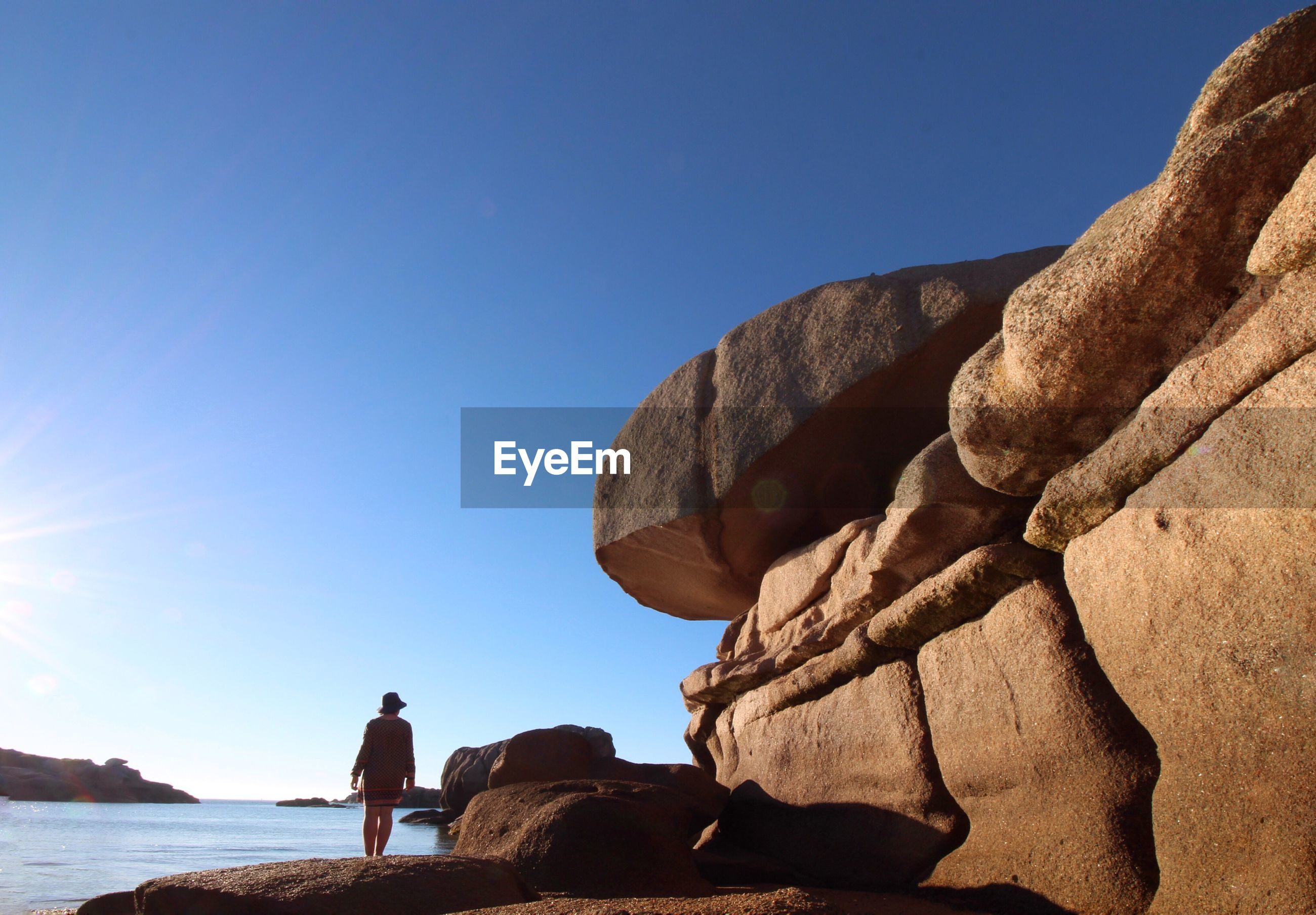 Rear view of woman standing by rock formation at sea against clear blue sky