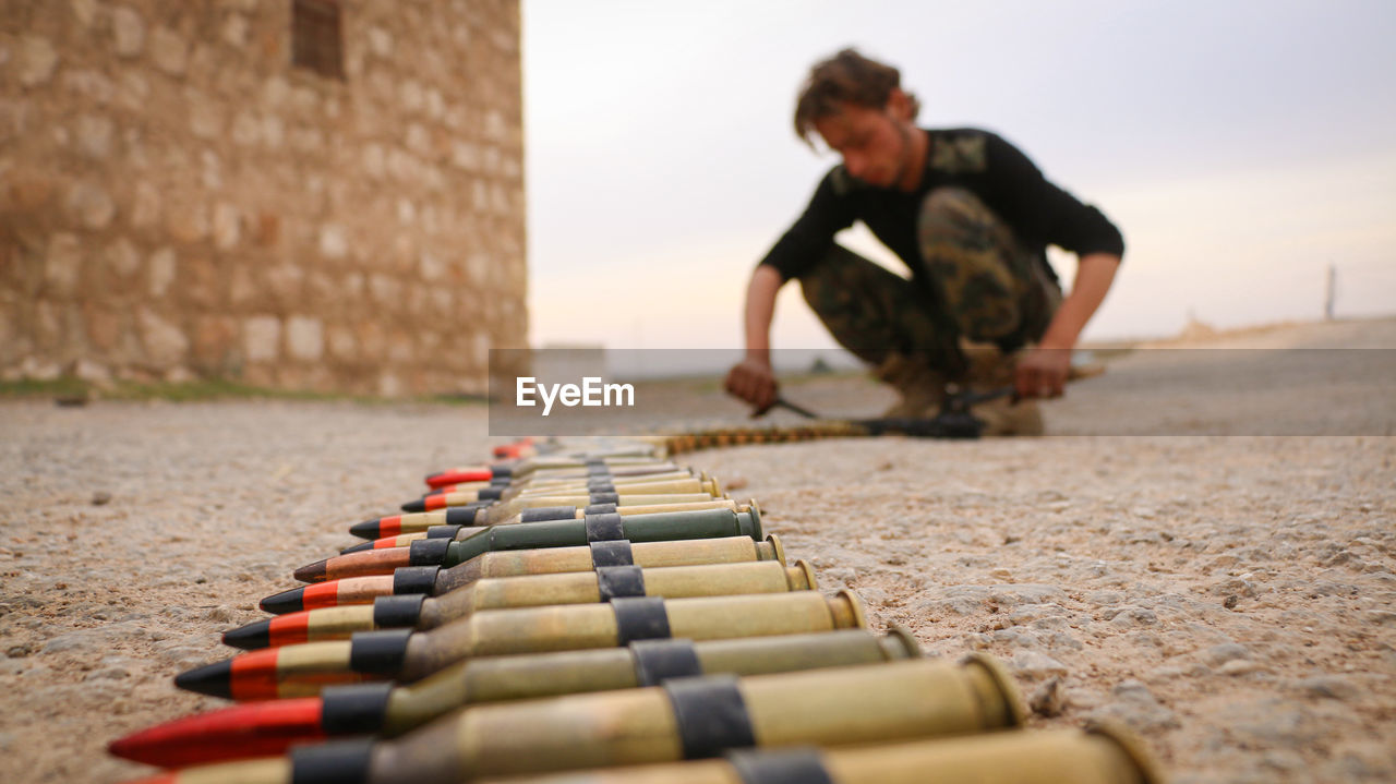 Full length of man arranging bullets on land against sky