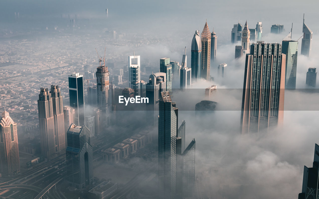 High angle view of skyscrapers in dubai's financial district amongst the early morning fog