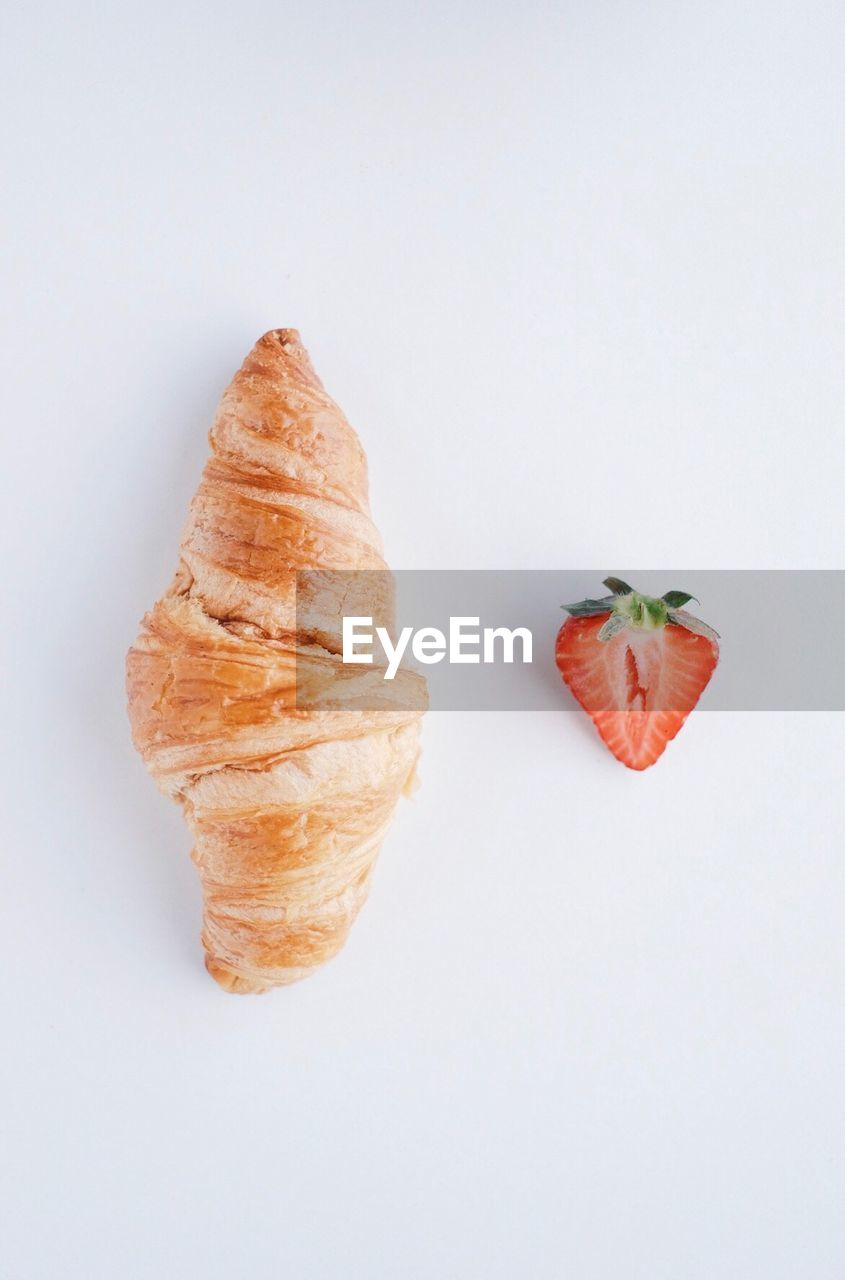 Close-Up Of Croissant And Strawberry On White Background