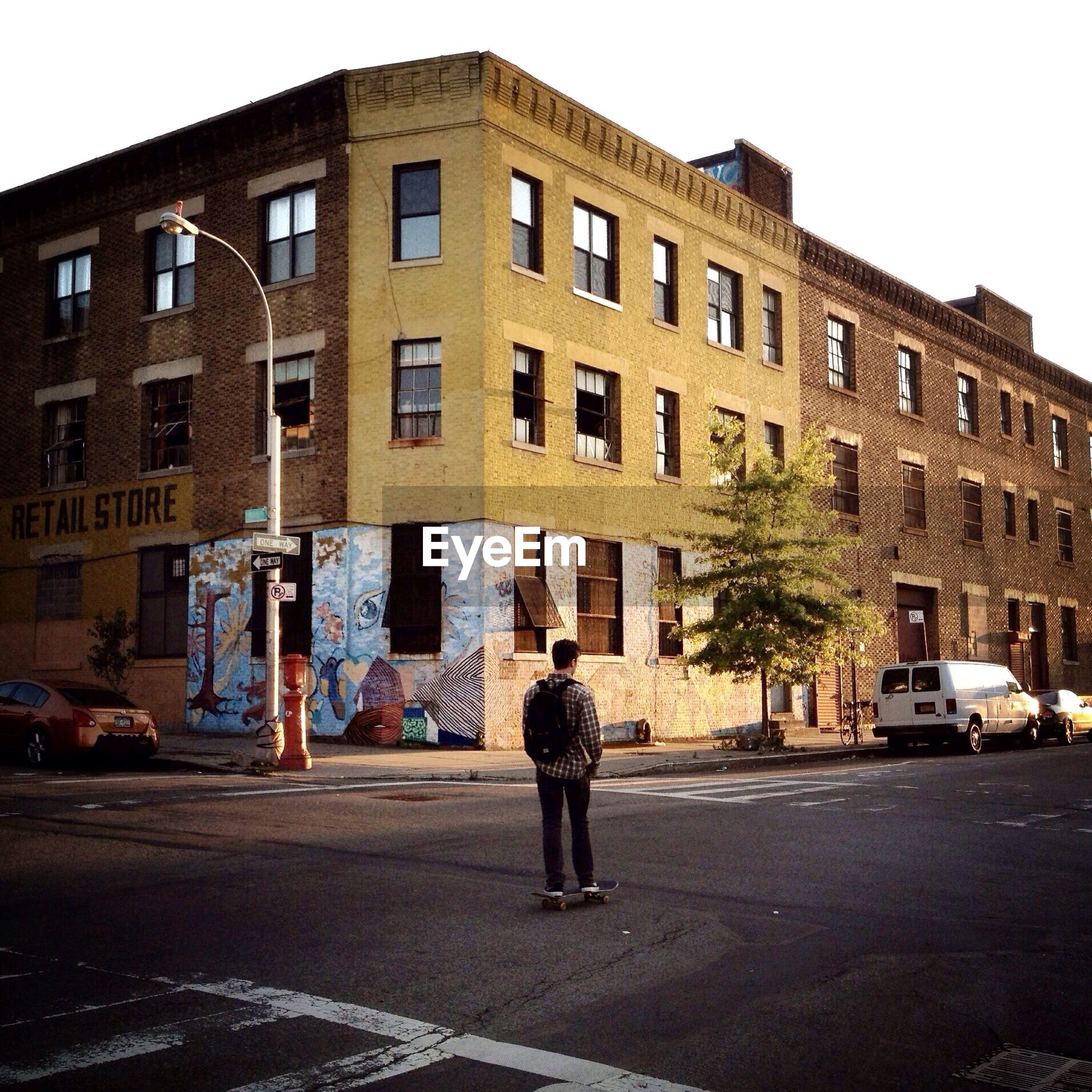 Rear view of man standing on road beside building
