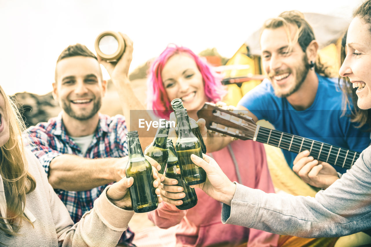 Male and female friends toasting beer bottles at beach