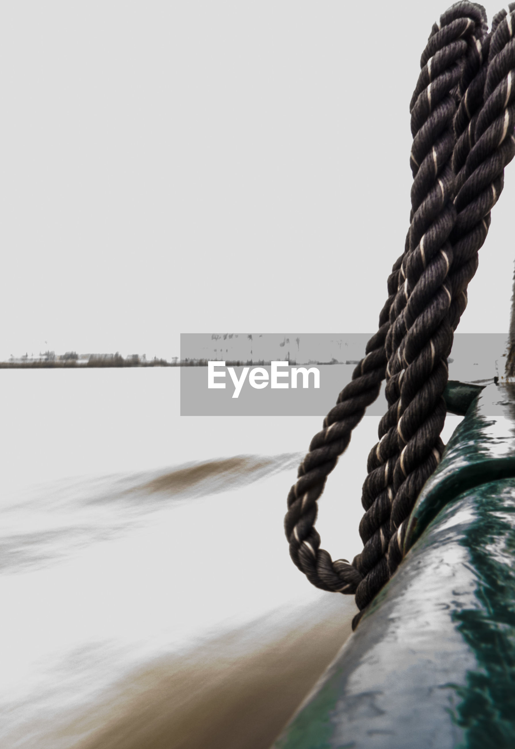 Rope hanging on boat sailing in sea against clear sky