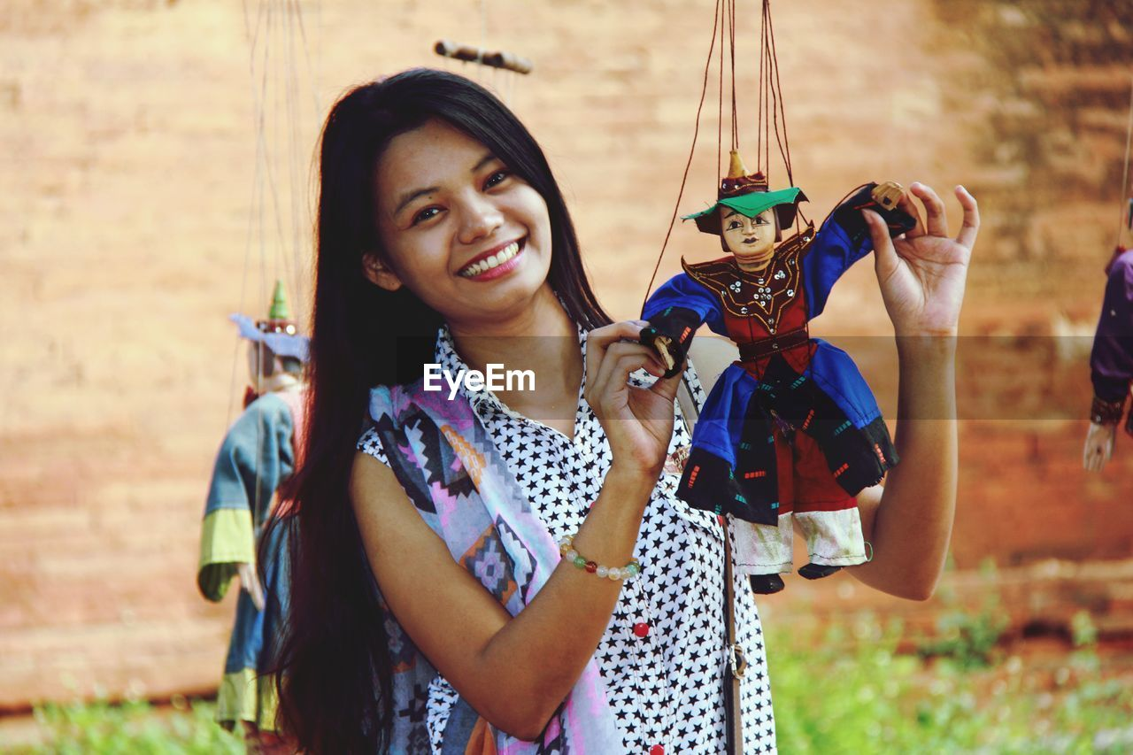 Portrait of smiling young woman holding puppet on field