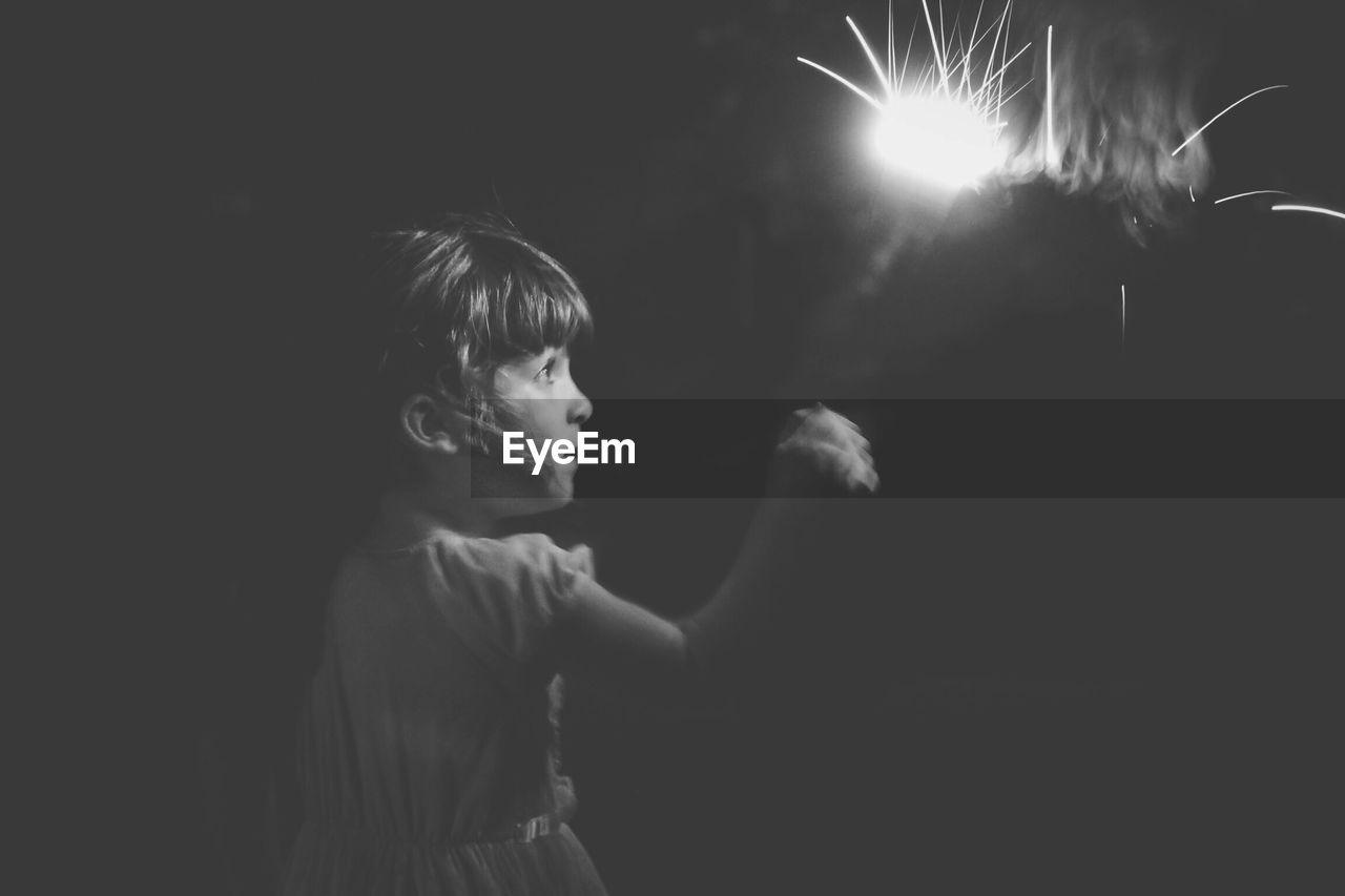 Side view of girl holding lit sparkler at night