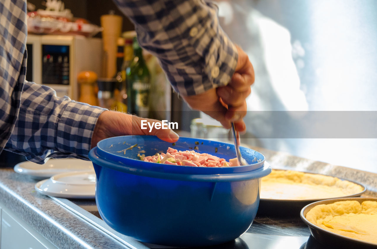 food and drink, real people, food, one person, bowl, indoors, freshness, holding, midsection, preparation, hand, focus on foreground, human hand, table, preparing food, lifestyles, unrecognizable person, selective focus, men, tray