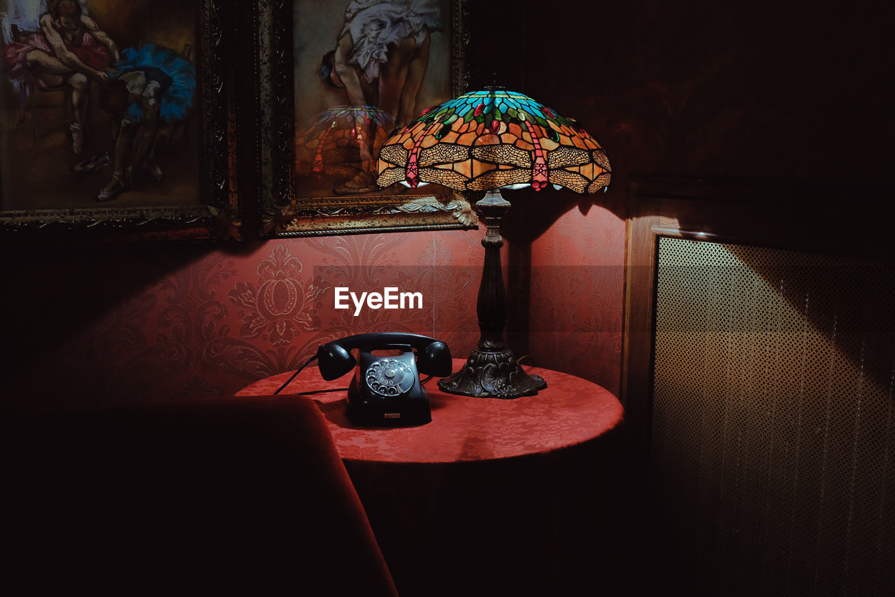 electric lamp, lighting equipment, indoors, retro styled, lamp shade, no people, technology, table, home interior, telephone, illuminated, wall - building feature, close-up, communication, time, antique, light, furniture, old, clock, side table, ornate, floral pattern