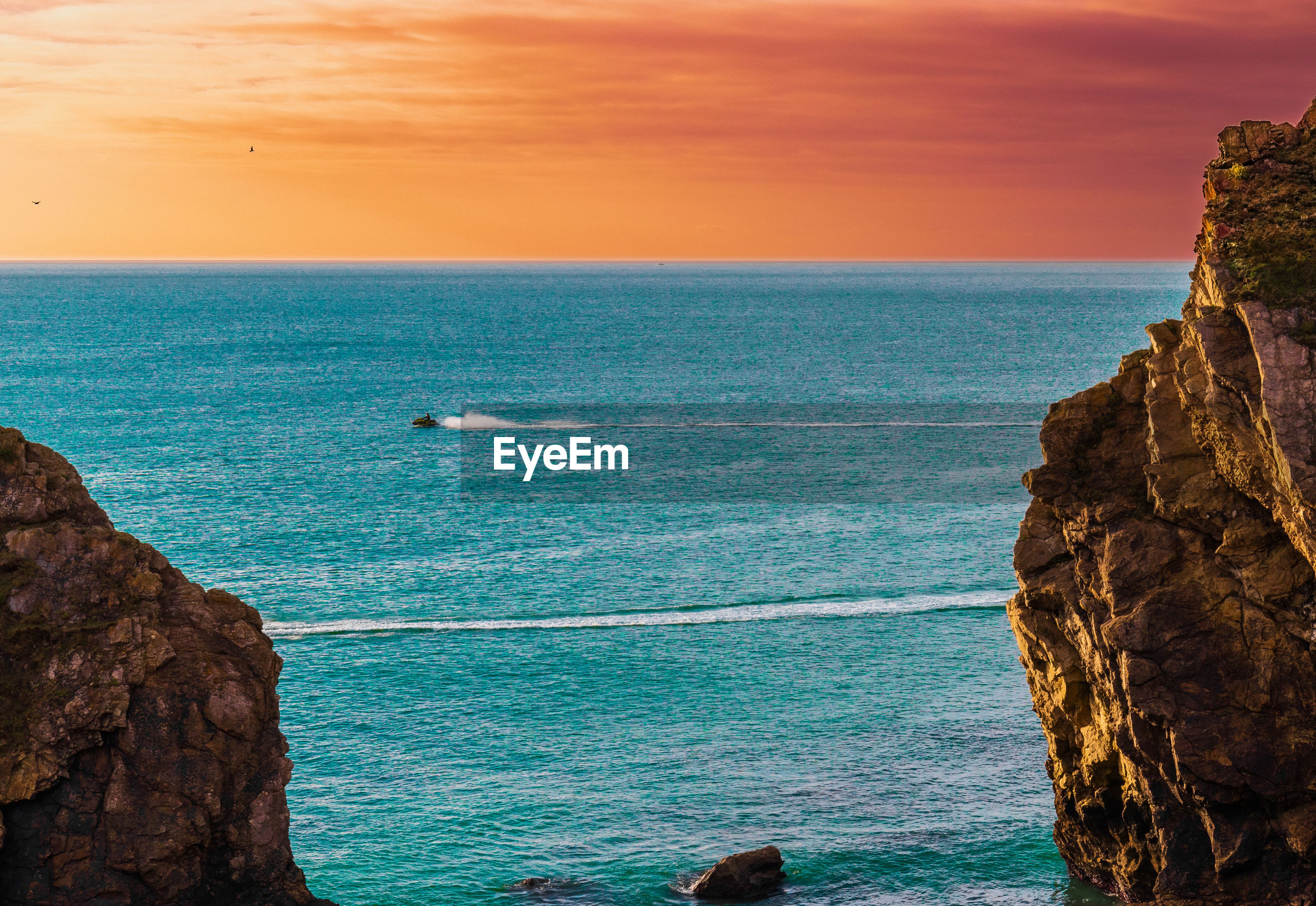 Scenic view of sea against sky during sunset, teal and orange